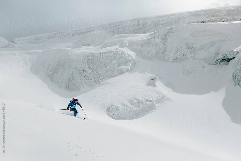 young male freerider skiing down a powder hill in a glacier  by Jordi Rulló for Stocksy United