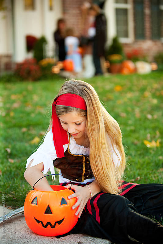 Halloween: Pirate Girl Checks Out Candy Bucket by Sean Locke for Stocksy United