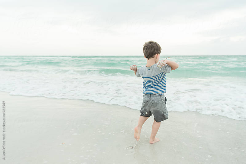 A Boy Throwing Sand Into The Water by Alison Winterroth for Stocksy United