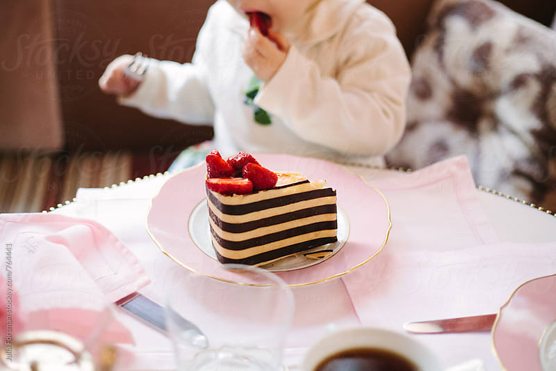 A little girl and a big slice of stripy cake with strawberries. by Julia Forsman for Stocksy United