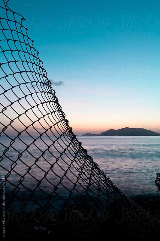 Broken fence silhouetted against a beautiful twilight Caribbean sky by anya brewley schultheiss for Stocksy United
