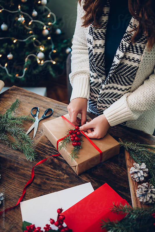 Woman Decorates a Christmas Present by Lumina for Stocksy United
