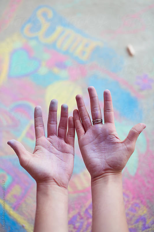 A young chalk artists dusty hands above a colourful pavement chalk drawing by Jacqui Miller for Stocksy United