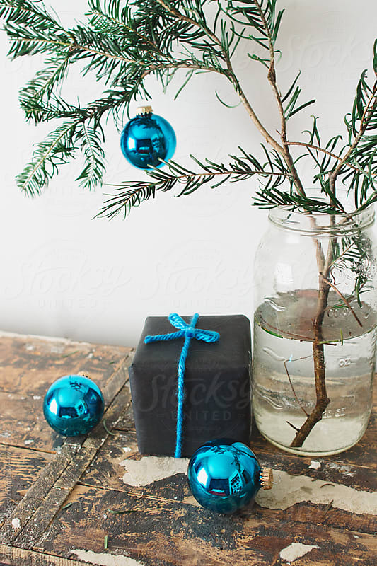 small gift and ornaments sit by simple pine branch in jar by Tana Teel for Stocksy United