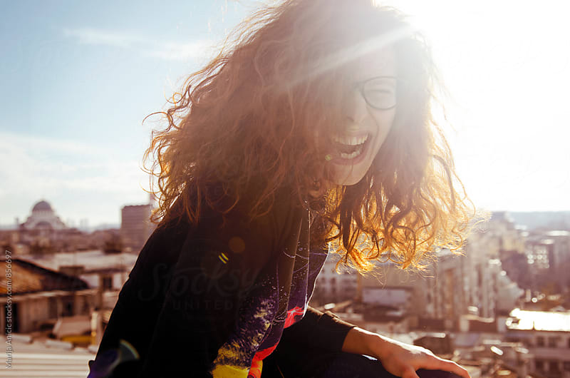 Redhead girl dancing and laughing on the rooftop by Marija Anicic for Stocksy United