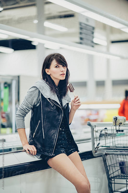Girl eating a popsicle in a supermarket by Ania Boniecka for Stocksy United