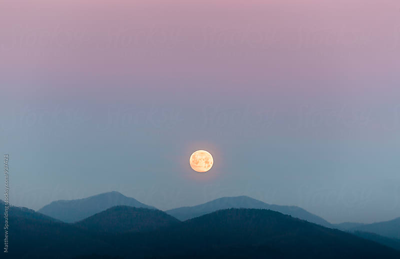 Moon setting into mountains under colorful sky by Matthew Spaulding for Stocksy United
