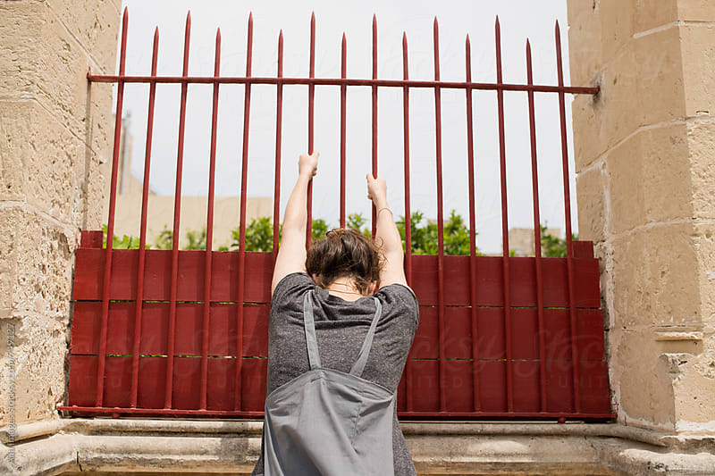 Tourist exploring old city climbing over wall breaking rules by Aila Images for Stocksy United