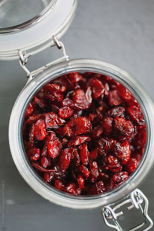 Cranberries: Closeup of an open jar of dried cranberries.  by Darren Muir for Stocksy United