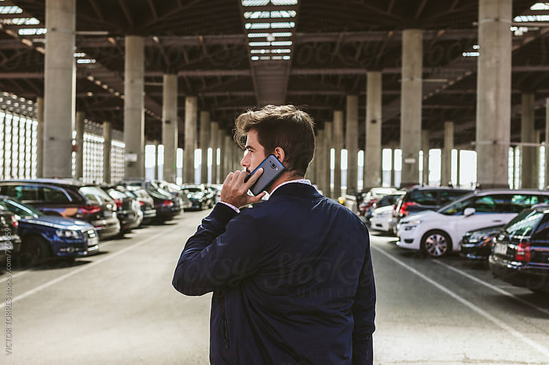 Elegant Young Businessman Talking by Phone in an Outdoor Car Parking by Victor Torres for Stocksy United