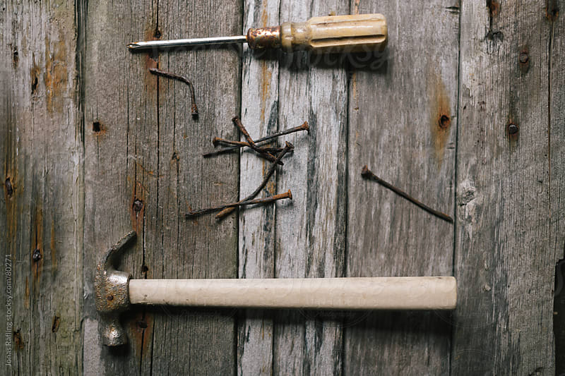 Old tools with rosty nails with the background of weather worn p by Jonas Räfling for Stocksy United