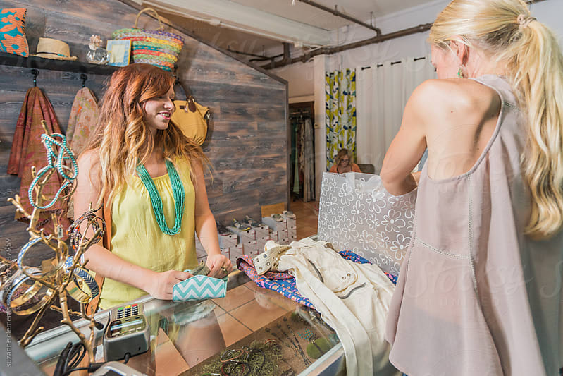 Woman Buys Clothes at a Fashionable Retail Boutique by suzanne clements for Stocksy United