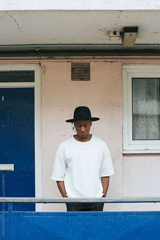 Outdoor Portrait of Young Stylish Black Man With Hat in Front of Run-Down Building by Julien L. Balmer for Stocksy United