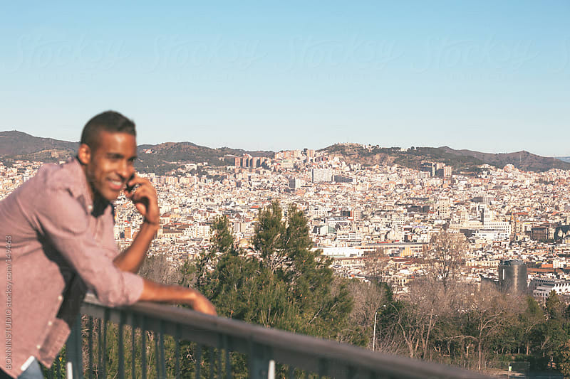 Black young man making a phone call. Nice panorama of Barcelona, Spain.  by BONNINSTUDIO for Stocksy United