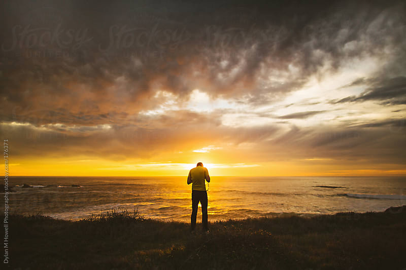Man with camera taking photographs of the ocean at sunset by Dylan M Howell Photography for Stocksy United