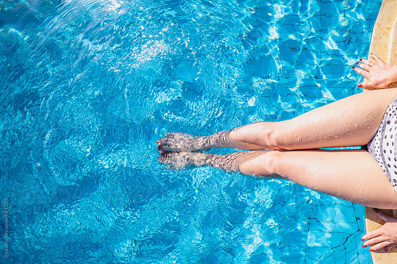 Legs of a woman sitting on the edge of pool by Ilya for Stocksy United