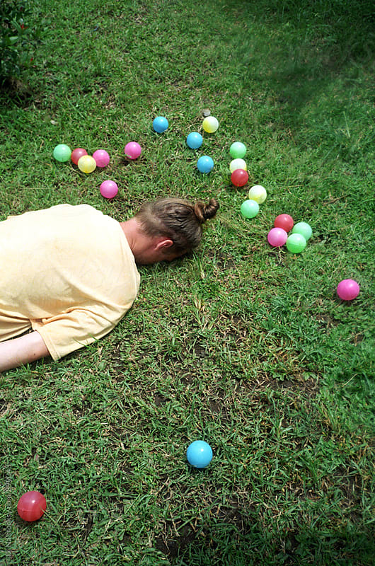 Young man lying on the ground face down surrounded by colorful balls by Dina Lun for Stocksy United
