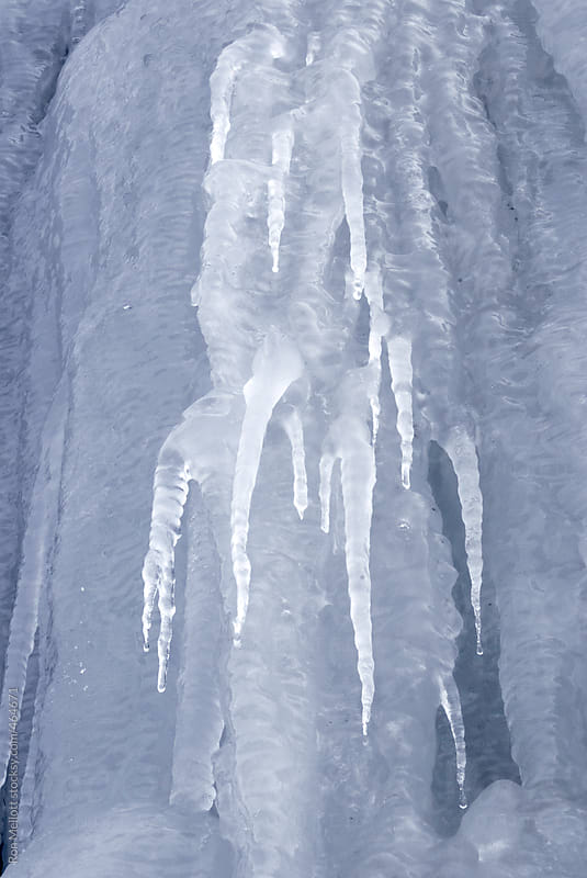 closeup macro of icicles created by groundwater runoff at road cut, frozen patterns by Ron Mellott for Stocksy United
