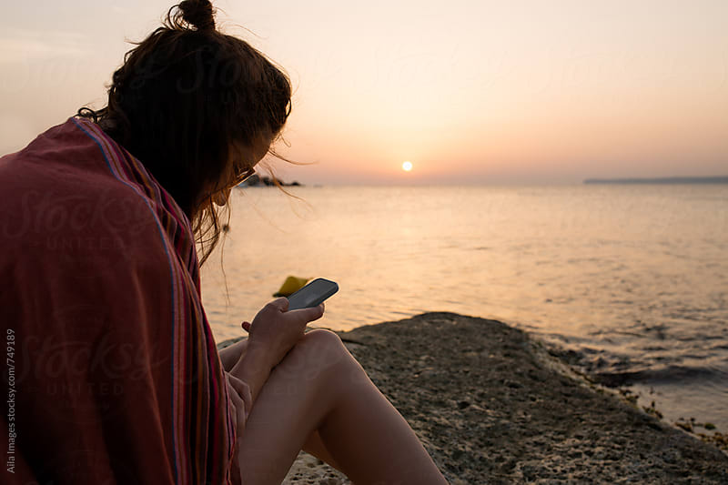 Woman watching sunset over ocean on vacation sharing on smart phone by Aila Images for Stocksy United