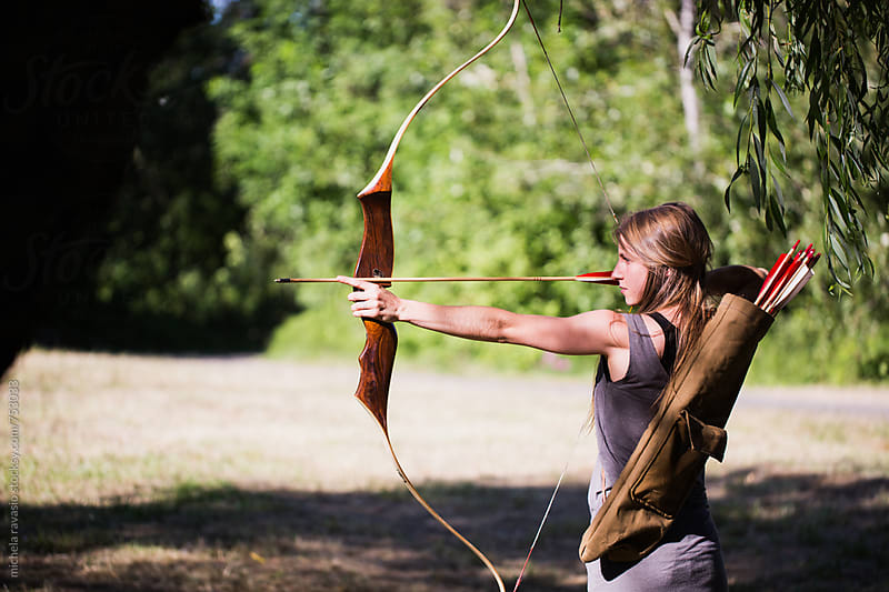 Woman taking aim with bow and arrow by michela ravasio for Stocksy United