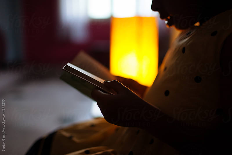 Silhouette of little girl reading a book by Saptak Ganguly for Stocksy United