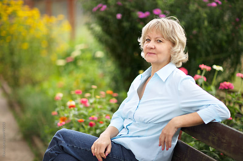 Mature woman sitting on bench in her garden relaxing by Ilya for Stocksy United