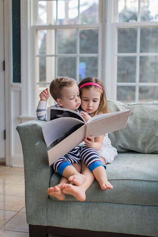 Young girl and boy toddler sitting on an oversized chair reading a book by Jakob for Stocksy United