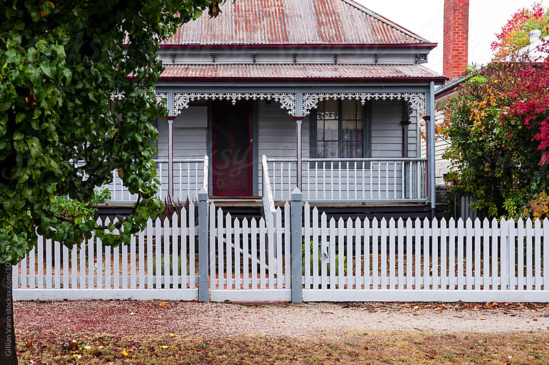 traditional timber cottage with white picket fence by Gillian Vann for Stocksy United