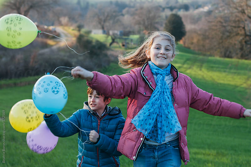 Children running and playing with ballons by Beatrix Boros for Stocksy United