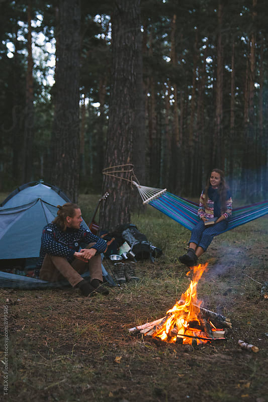 Couple sitting near campfire in forest by Danil Nevsky for Stocksy United