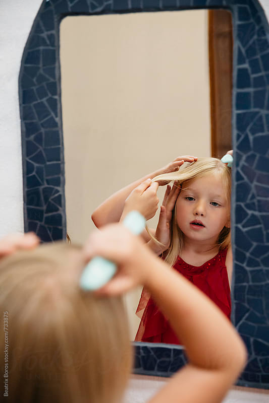 Little girl brushing her hair in front of a mirror by Beatrix Boros for Stocksy United