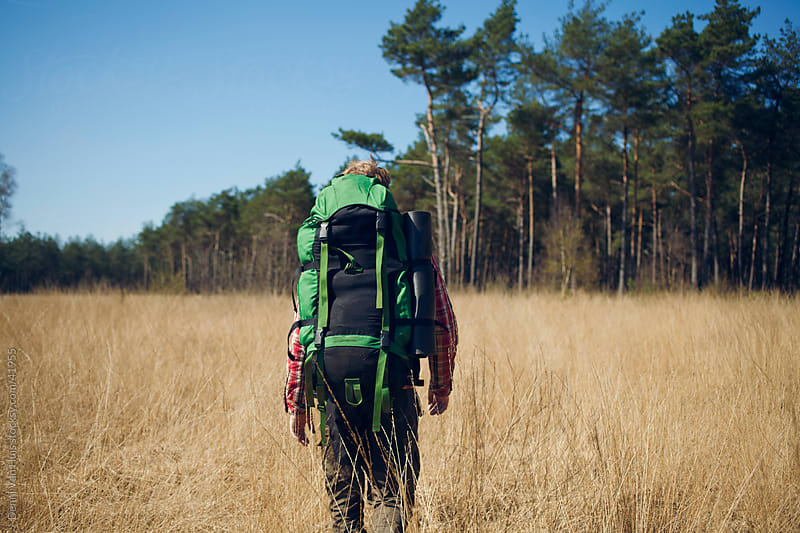 A man walking with a big backpack on through high grass by Denni Van Huis for Stocksy United