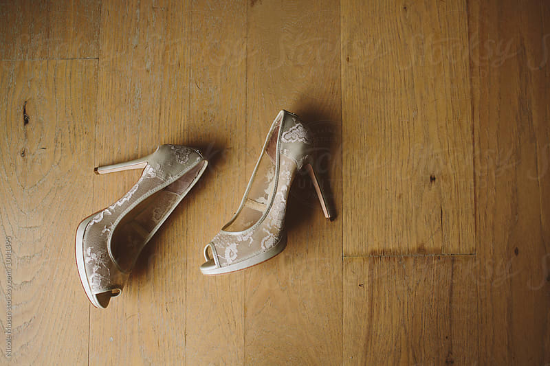 lacy bride wedding shoes laying on hardwood floor by Nicole Mason for Stocksy United