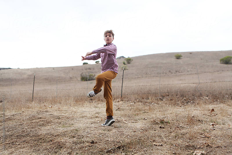 Boy Doing  Pirouette In Empty Field by Dina Giangregorio for Stocksy United