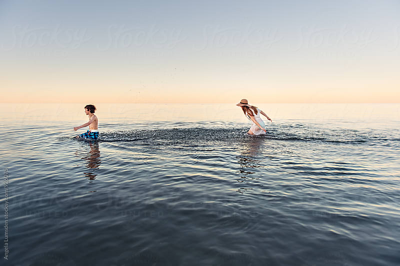 Girl chasing and splashing her brother in calm water at dusk by Angela Lumsden for Stocksy United