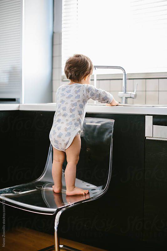 Rear view of  a 1 year old boy playing with water in the kitchen by Nasos Zovoilis for Stocksy United