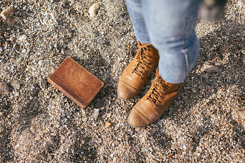 Closeup of woman boots and old book in the sand of beach. by BONNINSTUDIO for Stocksy United