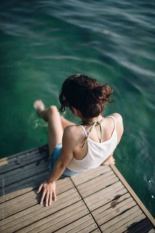 Woman relaxing on the pier by michela ravasio for Stocksy United