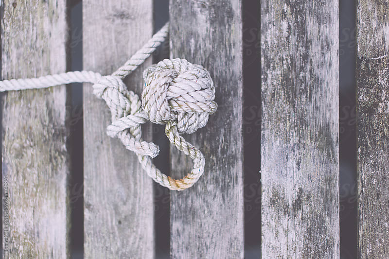 A Monkey's fist made of rope on a old jetty by Jonas Räfling for Stocksy United