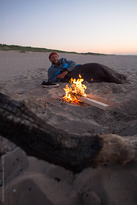 Young man laying net to bonfire on the beach in a sleeping bag by Denni Van Huis for Stocksy United