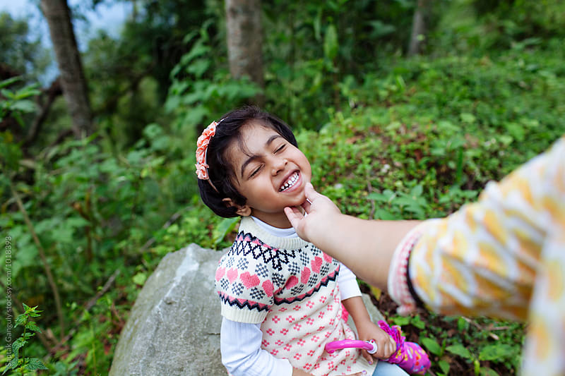 Mother caressing her daughter's chin outdoors by Saptak Ganguly for Stocksy United