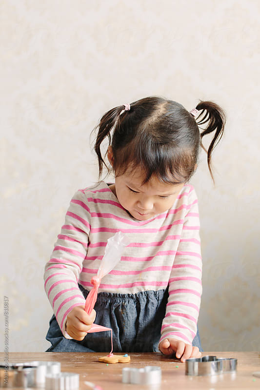 Toddler decorating cookie by Maa Hoo for Stocksy United
