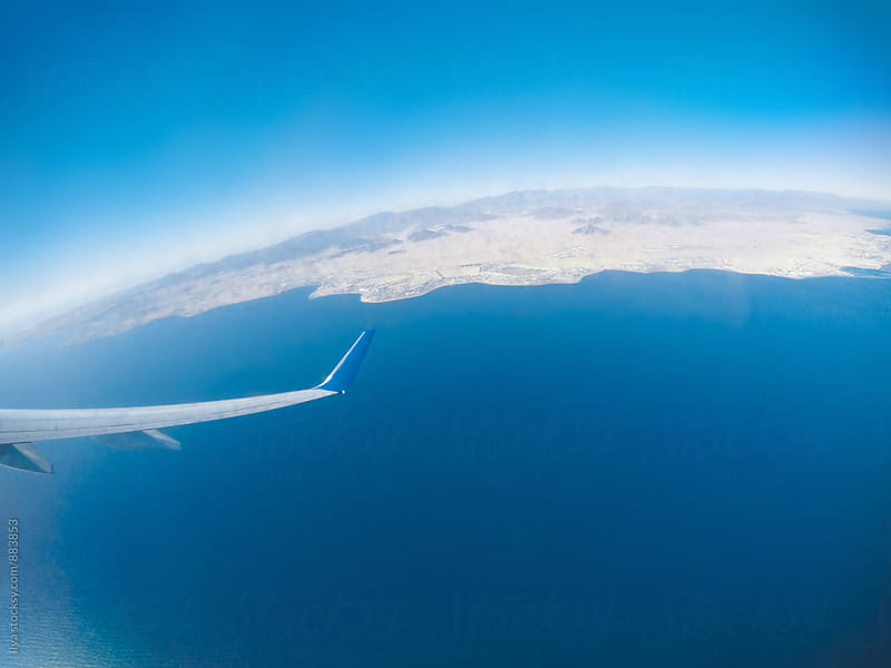 View of the plane wing, desert and sea shot through airplane window by Ilya for Stocksy United