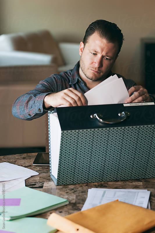 Taxes: Man Working At Home On Tax Preparation by Sean Locke for Stocksy United