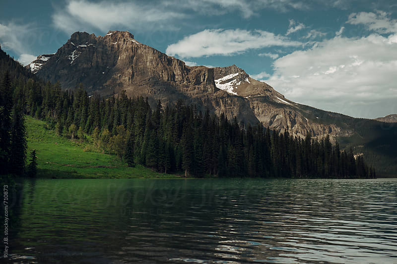A grassy clearing next to a mountain on a lake. by Riley J.B. for Stocksy United