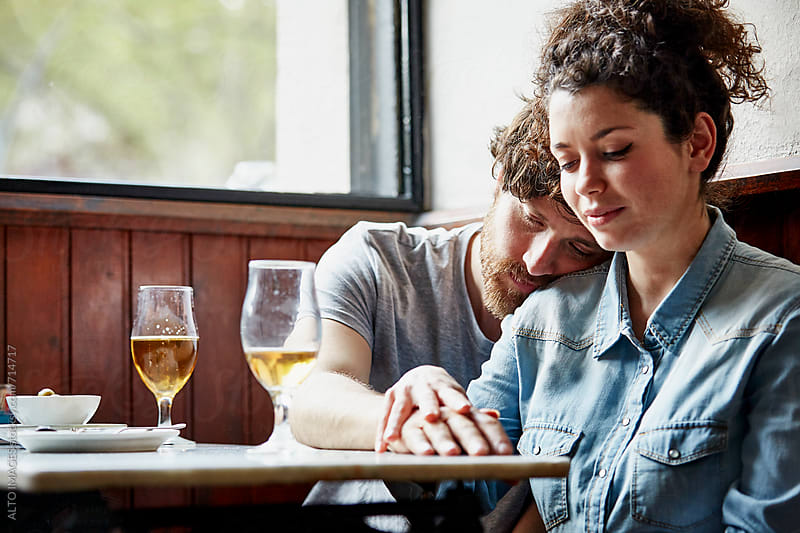 Man Resting Head On Woman's Shoulder In Restaurant by ALTO IMAGES for Stocksy United