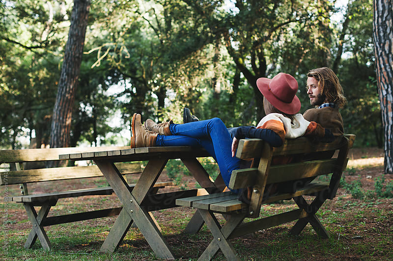 Side view of a couple sitting on a bench in the forest. by BONNINSTUDIO for Stocksy United