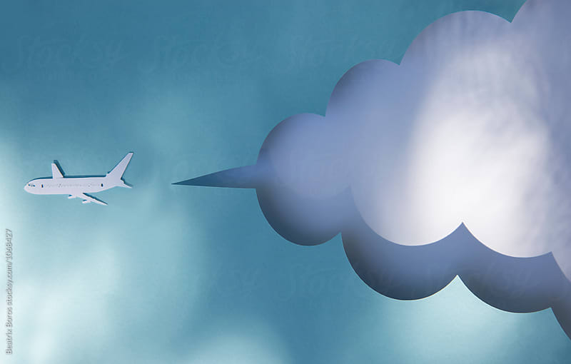 Cardboard airplane flying in front of a cloud mockup in shadow and light by Beatrix Boros for Stocksy United