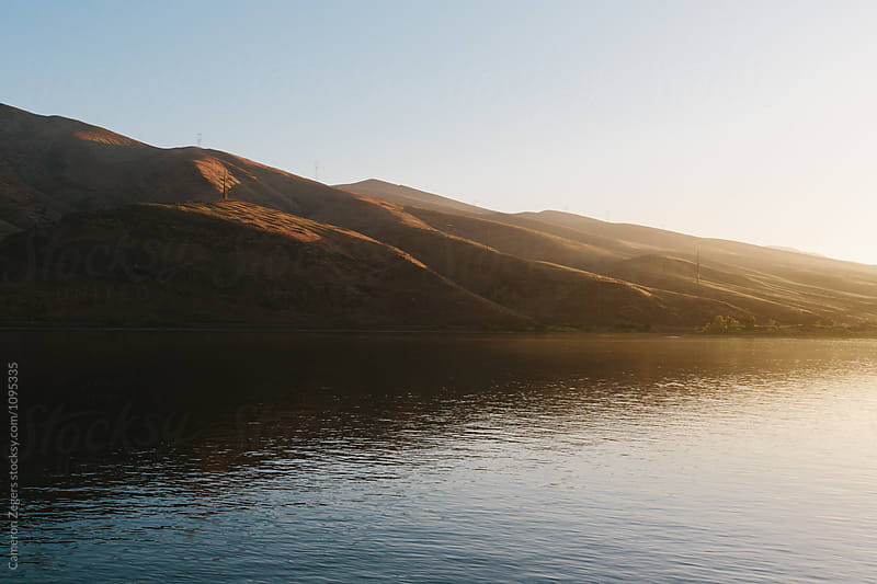 golden evening light on hills along river by Cameron Zegers for Stocksy United