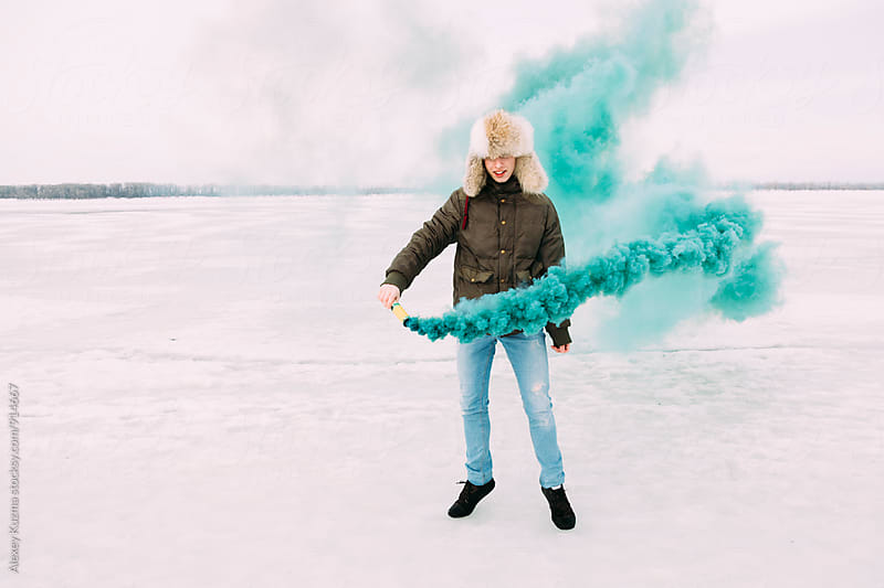 young man play with green smoke bomb by Vesna for Stocksy United